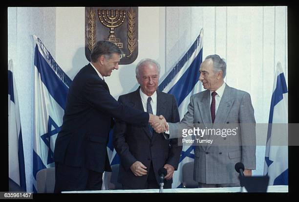 Israeli Foreign Minister Shimon Peres shakes hands with Norwegian Foreign Minister Johan Jorgen Holst at the signing of the peace agreement between...