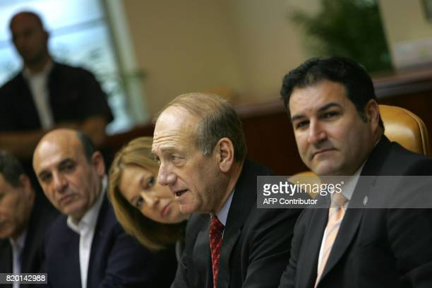 Israeli Foreign Minister Tsipi Livni looks over Prime Minister Ehud Olmert's shoulder as he makes his opening remarks at the start of the weekly...