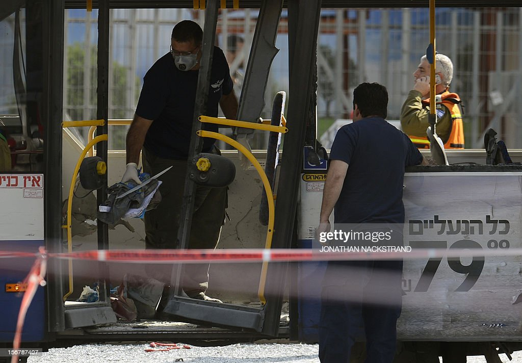 Israeli forensic experts inspect a bus which was hit by a bomb near the defence ministry in Tel Aviv on November 21, 2012. At least 10 people were injured in an explosion on a bus, Israel's emergency services said, in what an official said was 'a terrorist attack.' AFP PHOTO / JONATHAN NACKSTRAND