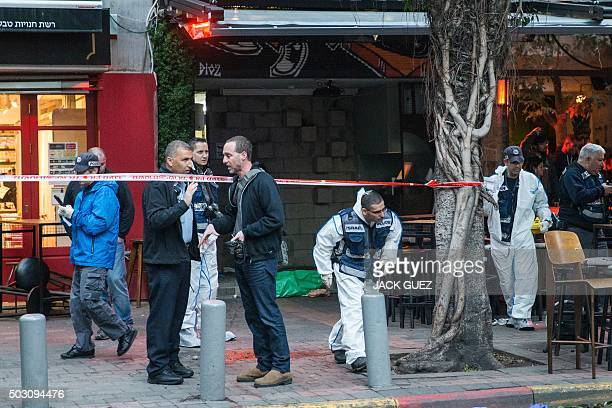 Israeli forensic experts work outside a pub following an attack by an unidentified gunman who opened fire killing two people and wounding at least...