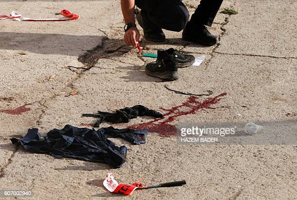 TOPSHOT Israeli forensic police gather at the scene of a stabbing attack where a Palestinian stabbed an Israeli soldier before he was shot dead in...