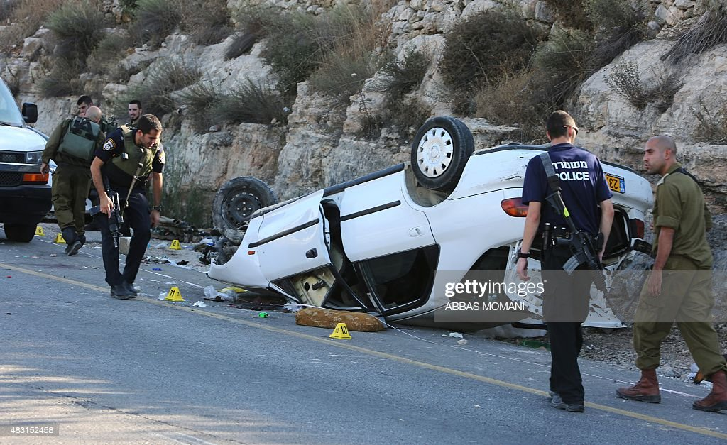 Israeli forensic policemen and security forces inspect the scene of a car attack at a junction midway between Ramallah and Nablus in the...