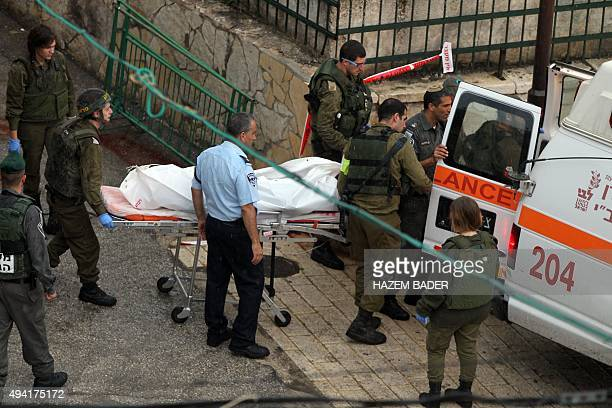 Israeli forensic policemen wheel away the body of a Palestinian woman who was shot dead by Israeli borderguards after attempting to stab officers at...