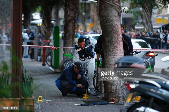 Israeli forensics inspect the site of an attack by an unidentified gunman who opened fire at a pub in the Israeli city of Tel Aviv killing two people...