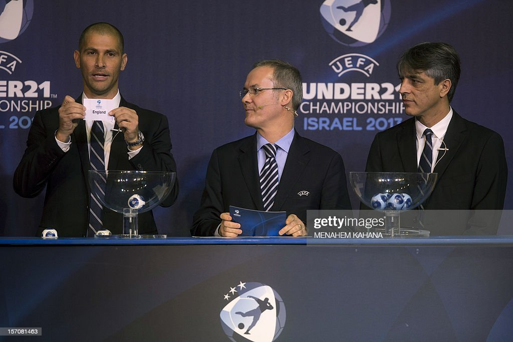 Israeli former football player Eli Ohana (R) and Union of European Football Associations (UEFA) director Giorgio Marchetti (C) look on as football player Avi Nimni (L) holds up the name draw 'England' during the draw ceremony for the final round of the 2013 UEFA European Under-21 Championship, at the Hilton Hotel in Tel Aviv, on November 28, 2012.