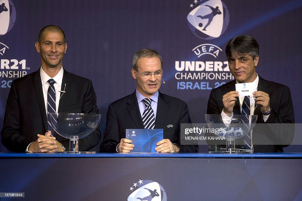 Israeli former football player Eli Ohana (R) holds up the name draw as football player Avi Nimni (L) and Union of European Football Associations (UEFA) director Giorgio Marchetti (C) attend the draw ceremony for the final round of the 2013 UEFA European Under-21 Championship, at the Hilton Hotel in Tel Aviv, on November 28, 2012.