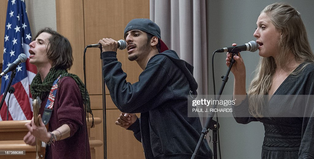 Israeli guitarist Guy Gefen(L), Palestinian rapper Moody Kablawi(C), and Israeli vocalist Kela Sappir, perform with 'Heartbeat' November 8, 2013 inside the US Department of State in Washington. The Jerusalem-based band unites Israeli and Palestinian youth musicians and are starting their second US tour to build understanding. AFP PHOTO/Paul J. Richards