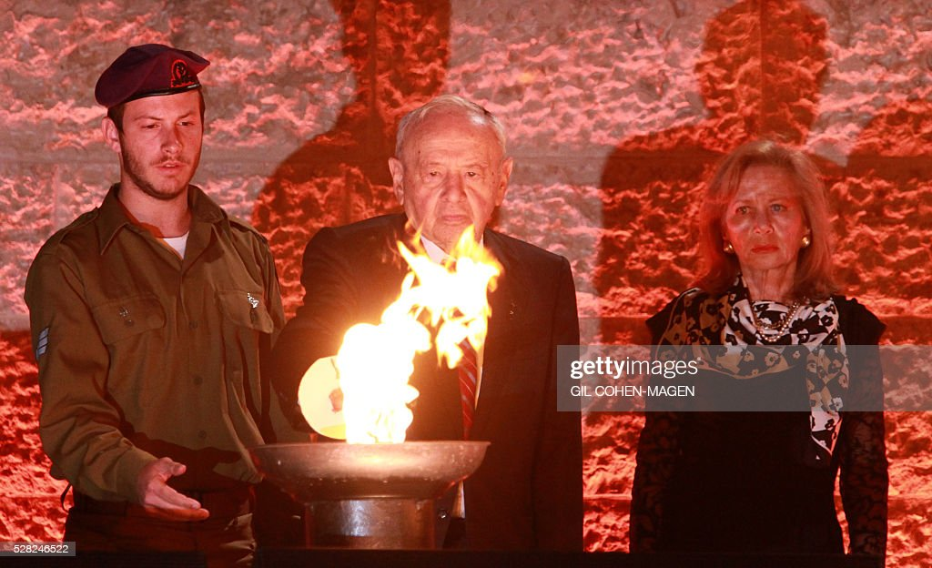 Israeli Holocaust survivor Joshua Hessel Fried (C) and his grandson Lee-oz Fried (L) light one of the six torches in memory of the victims during a ceremony marking the Holocaust Remembrance Day on May 4, 2016 at the Yad Vashem Holocaust memorial in Jerusalem. Holocaust Remembrance Day, commemorating the six million Jews killed by the Nazis during World War II, is an internationally recognized date corresponding to the 27th day of Nisan on the Hebrew calendar and begins this year in the evening of May 4 and ends in the evening of May 5. / AFP / Gil Cohen-Magen