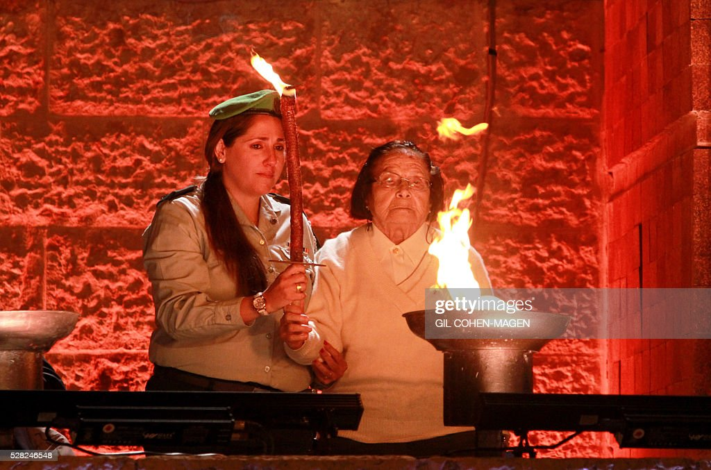 Israeli Holocaust survivor Sara Kain (R) and her granddaughter Einat Elbalek light one of the six torches in memory of the victims during a ceremony marking the Holocaust Remembrance Day on May 4, 2016 at the Yad Vashem Holocaust memorial in Jerusalem. Holocaust Remembrance Day, commemorating the six million Jews killed by the Nazis during World War II, is an internationally recognized date corresponding to the 27th day of Nisan on the Hebrew calendar and begins this year in the evening of May 4 and ends in the evening of May 5. / AFP / Gil Cohen-Magen