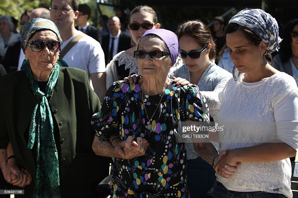 Israeli holocaust survivors who survived Auschwitz death camp stand still as sirens sounded across Israeli for a two-minute silence in memory of Holocaust victims during a ceremony marking the annual Holocaust Remembrance Day at the Yad Vashem Holocaust Memorial in Jerusalem on May 5, 2016. The state of Israel marks the annual Memorial Day commemorating the six million Jews murdered by the Nazis in the Holocaust during World War II. / AFP / GALI