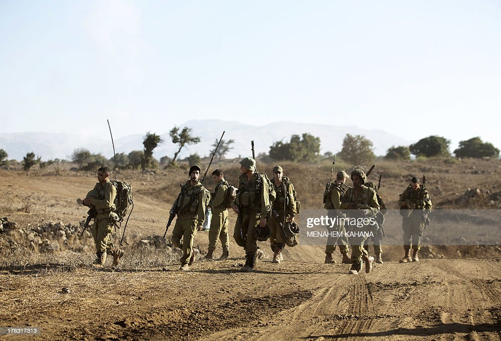 Israeli infantry soldiers walk in a deployment training area in the Israeli-annexed Golan Heights near the border with Syria on August 29, 2013