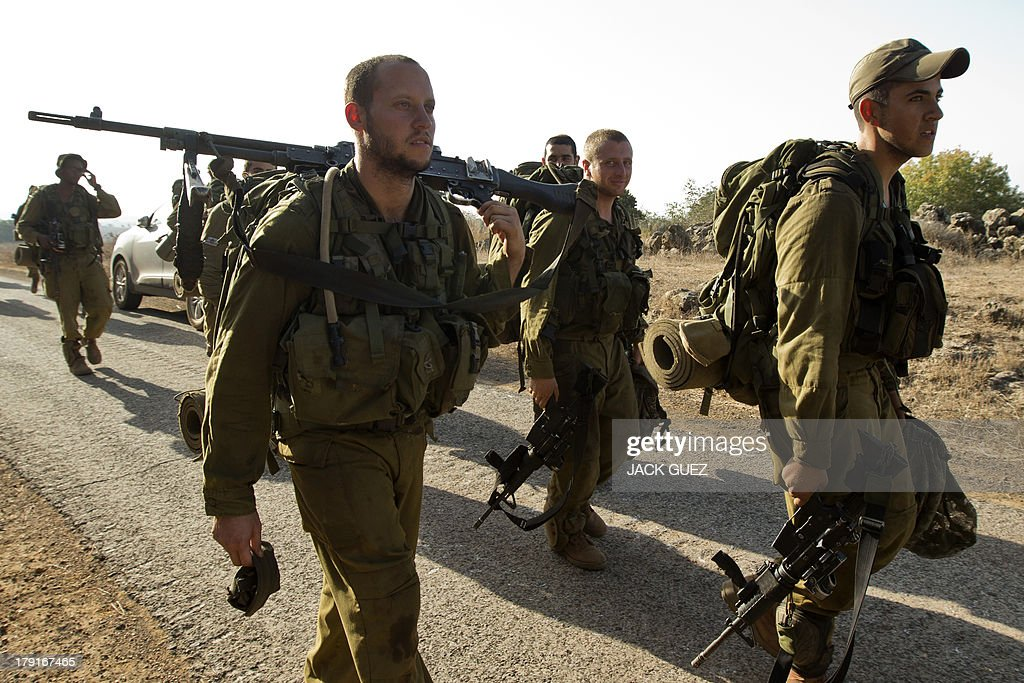 Israeli infantry soldiers walk in a deployment training area in the Israeli-annexed Golan Heights near the border with Syria on September 1, 2013. The Israeli cabinet authorised on August 28 a partial call-up of army reservists amid growing expectations of a foreign military strike on neighbouring Syria, army radio reported. The unspecified number of troops are attached to units stationed in the north of the country, which borders both Lebanon and the Golan Heights.