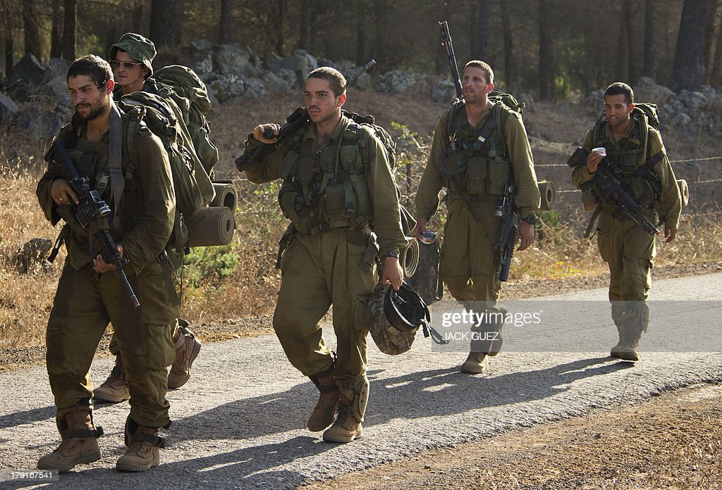 Israeli infantry soldiers walk in a deployment training area in the Israeli-annexed Golan Heights near the border with Syria on September 1, 2013. The Israeli cabinet authorised on August 28 a partial call-up of army reservists amid growing expectations of a foreign military strike on neighbouring Syria, army radio reported. The unspecified number of troops are attached to units stationed in the north of the country, which borders both Lebanon and the Golan Heights. AFP PHOTO / JACK GUEZ