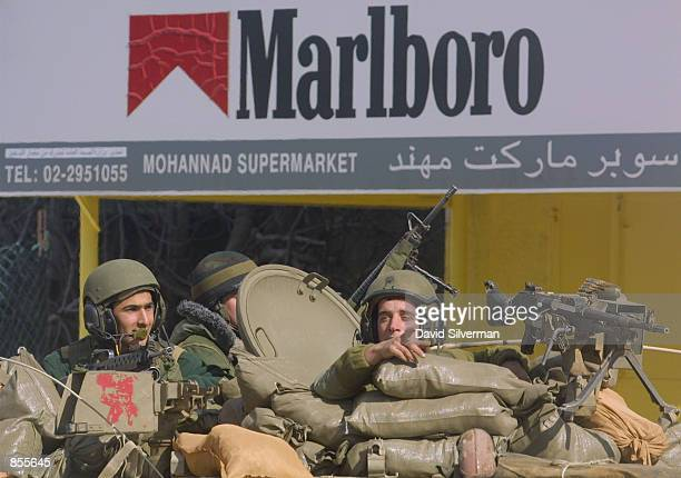 Israeli infantry troops ride their Armored Personnel Carrier to their position opposite Palestinian leader Yasser Arafat's offices January 20 2002 in...