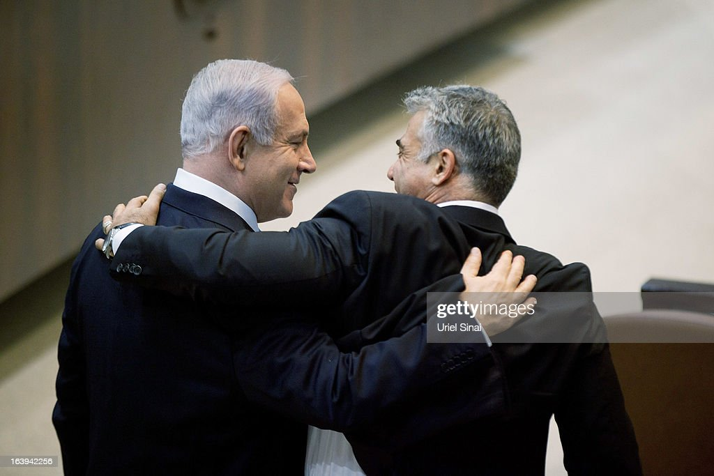 Israeli Israeli Prime Minister <a gi-track='captionPersonalityLinkClicked' href=/galleries/search?phrase=Benjamin+Netanyahu&family=editorial&specificpeople=118594 ng-click='$event.stopPropagation()'>Benjamin Netanyahu</a> (L) hugs <a gi-track='captionPersonalityLinkClicked' href=/galleries/search?phrase=Yair+Lapid&family=editorial&specificpeople=5366792 ng-click='$event.stopPropagation()'>Yair Lapid</a>, leader of the Yesh Atid during a Knesset session on March 18, 2013 in Jerusalem, Israel. Israel's 33rd government is to be sworn in today after almost six weeks of negotiations to piece together a coalition government.