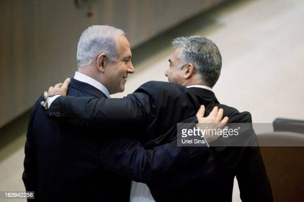 Israeli Israeli Prime Minister Benjamin Netanyahu hugs Yair Lapid leader of the Yesh Atid during a Knesset session on March 18 2013 in Jerusalem...
