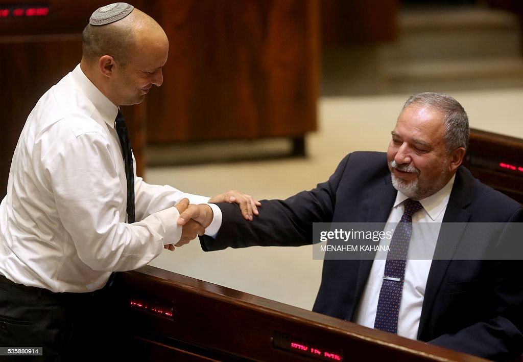 Israeli Jewish Home party leader Naftali Bennett (L) greets former Israeli foreign minister and ultra-nationalist MP Avigdor Lieberman during a session of the Israeli parliament in which MPs are debating whether to approve Lieberman's appointment as defence minister, on May 30, 2016 in Jerusalem. Israeli Prime Minister Benjamin Netanyahu's cabinet voted to expand his coalition and appoint hardliner Avigdor Lieberman as defence minister, bringing weeks of political intrigue -- and outrage -- towards a close. Parliament was expected later today to approve the appointment of Lieberman, a former foreign minister and ultra-nationalist who has pledged harsh measures against Palestinian 'terrorists'. KAHANA