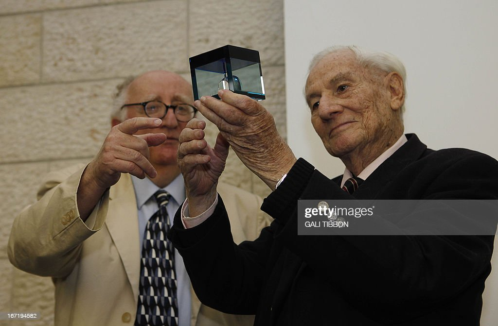 Israeli Justice Gabriel Bach (R), senior prosecutor in the Adolf Eichmann's trial and former Justice of the Supreme Court of Israel is given an award during a ceremony held in his honor by The Mensch International Foundation on April 22, 2013 at the Hebrew University of Jerusalem. The Mensch International Foundation honored Justice Gabriel Bach for the unique ways in which he has helped raise awareness of the Holocaust and its lessons worldwide. AFP PHOTO/GALI TIBBON