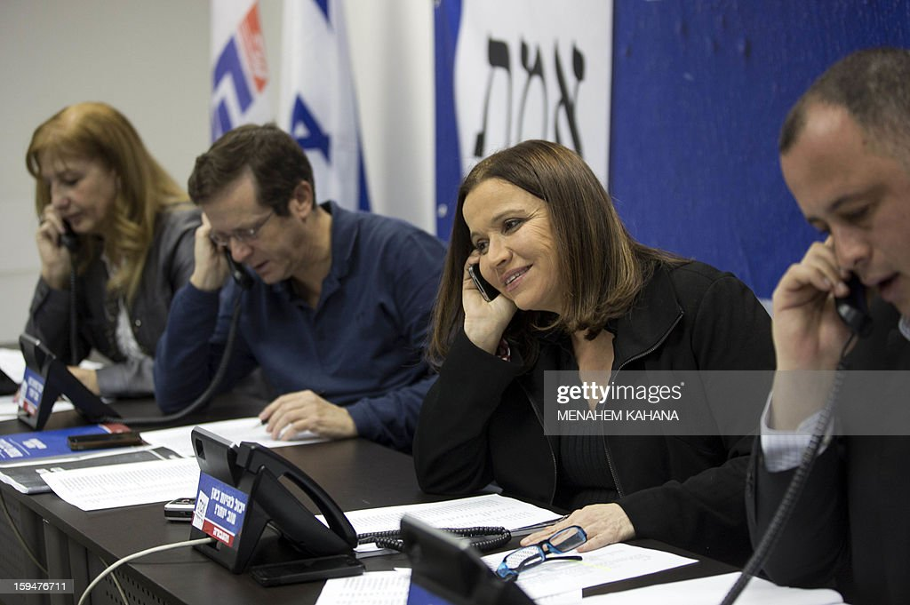 Israeli Labour party's leader and candidate for the general elections for the country's 19th Knesset Shelly Yachimovich (C) speaks on the phone with supporters alongwith her campaign staff on January 14, 2013 at a shopping mall in Tel Aviv. Israeli election will be held on January 22.