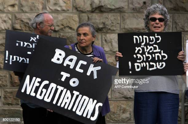 Israeli left wing protestor hold banners during a small demonstration against the Israeli offensive in Lebanon and Gaza in front of the residence of...