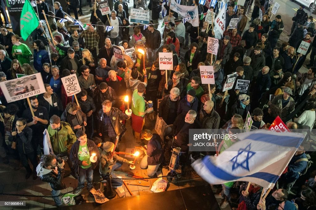Israeli leftwing activists take part in a 'Peace Now' march calling on Israelis to choose ''another way'' at the Rabin Square in the city of Tel Aviv...