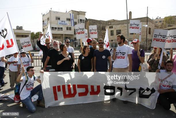 Israeli leftwing demonstrators hold banners in front of a Palestinian house occupied by Israeli settlers in the centre of the divided city of Hebron...