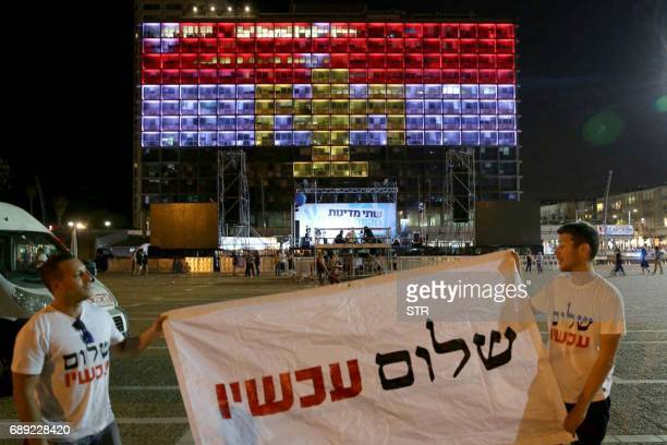 Israeli leftwing supporters hold a banner reading 'Peace' in Hebrew in front of the Tel Aviv Municipality building illuminated with the colours of...
