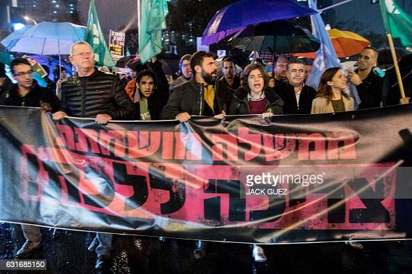 Israeli leftwing supporters hold banners reading in Hebrew ''Corrupt governments must go'' during a rally against Israeli Prime Minister Benjamin...