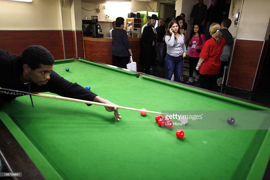 A Israeli man plays pool as others stand in a billiard room used as a shelter while air raid sirens sound November 19, 2012 in Ashdod, Israel. According to reports November 19, 2012, at least 90 Palestinians have been killed and more than 700 wounded during the Israeli offensive in the Gaza Strip.