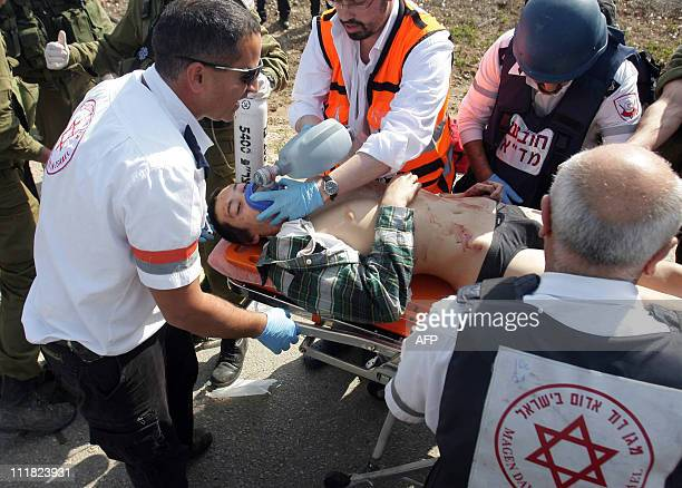 Israeli medics carry a teenager critically wounded by an antitank missile fired by Gaza militants that hit a school bus near the southern Israeli...