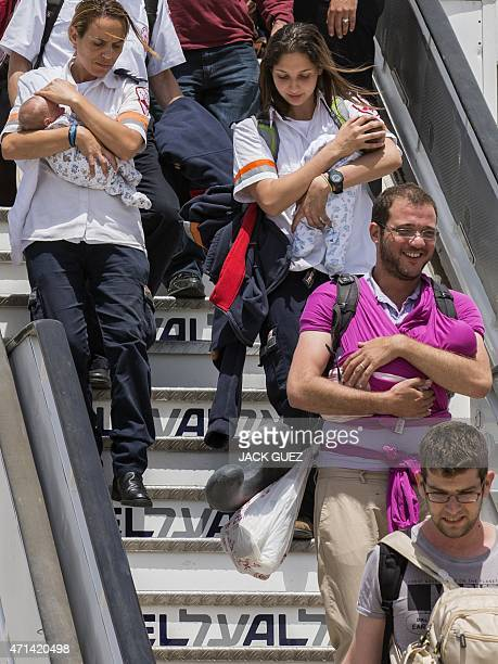 Israeli medics carry the babies of a homosexual couple who had three infants born to surrogate mothers in Nepal after they arrived at Ben Gurion...