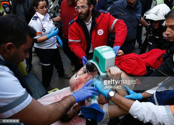 Israeli medics give emergency treatment to a victim following an attack by an unidentified gunman who opened fire at a pub in the Israeli city of Tel...