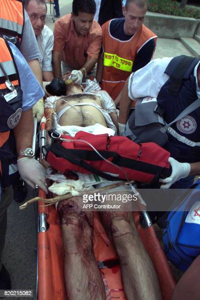 Israeli medics move on a stretcher an injured man following an explosion at the busy cafeteria in east Jerusalem's Hebrew University 31 July 2002 An...