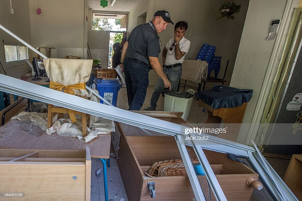 Israeli men talk as the stand amidst the debris caused by a rocket, fired by Palestinian militants from the Gaza Strip, after it landed in the courtyard of a kindergarten in the southern costal Israeli city of Ashdod, on August 26, 2014. Israel upped the pressure on Hamas, with warplanes hitting two Gaza City highrises on day 50 of their conflict as the warring parties mulled a new Egyptian truce proposal.