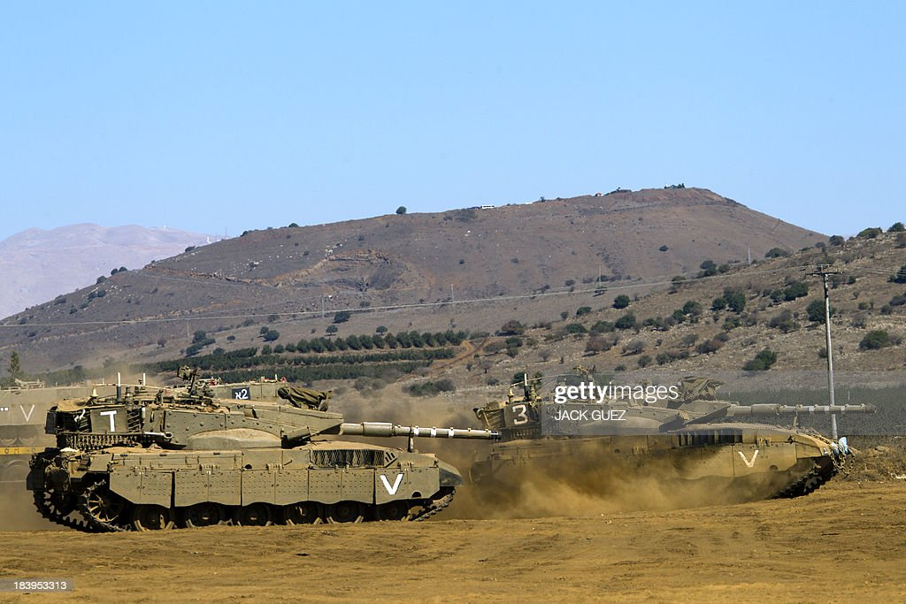 Israeli Merkava tanks roll in a training field in the Golan Heights, next to the Israeli-Syrian border, on October 10, 2013. The Israeli army fired on October 9, a Tammuz missile across the Syrian border in response to mortar fire from the Syrian at an Israeli military base in the northern Israeli-annexed Golan Heights leaving two soldiers with light wounds.