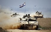 Israeli Merkava tanks roll near the border between Israel and the Gaza Strip as they return from the Hamascontrolled Palestinian coastal enclave on...