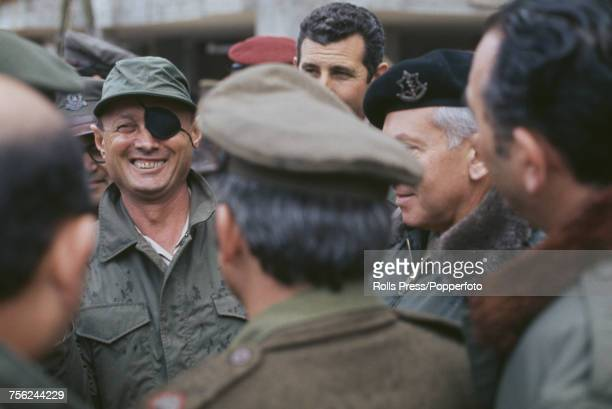 Israeli military leader and Defense Minister of Israel Moshe Dayan pictured wearing a military jacket as he talks with members of the Israel Defense...