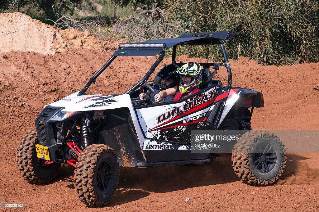 Israeli Minister of Sports and Culture Miri Regev (C-R) drives an ATV (all-terrain vehicle) as part of the inauguration of the MX Wingate Motocross track near the Israeli city of Netanya on February 11, 2016. / AFP / JACK GUEZ