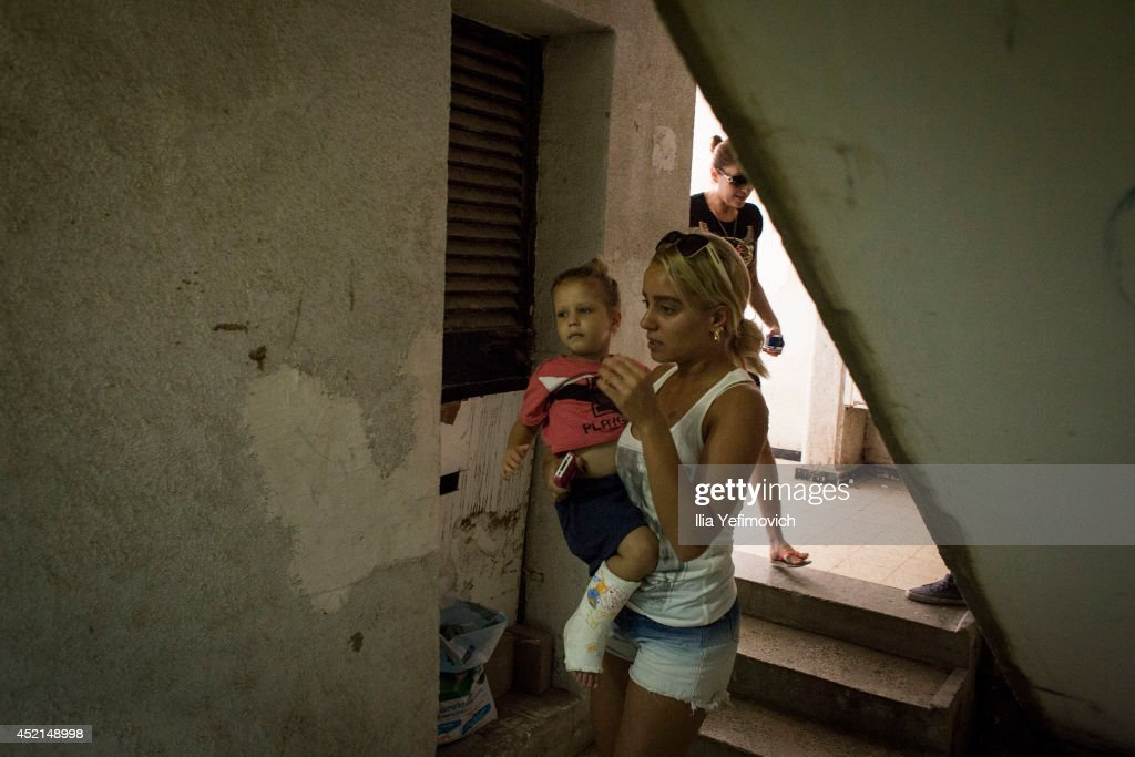 Israeli mother and son seen run to a bomb shelter as the siren goes off on July 14, 2014 at the city of Ashkelon. Israel's operation 'Protective Edge' has entered a seventh day as the Israel Defense Forces (IDF) continue to carry out massive airstrikes across the Gaza Strip with reports suggesting over 166 people have been killed, the majority of whom are civilians.