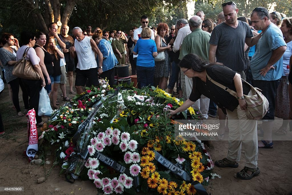 Israeli mourners stand next to the flower wreaths covering the grave of Shahar Melamed, 43, who was killed the previous day by Palestinian mortar fire in Kibbutz Nirim near Israel's border with the Gaza Strip, on August 27, 2014. Melamed and another Israeli civilian were killed and another two were wounded when a mortar round struck the kibbutz close to the Gaza border, shortly before a permanent ceasefire came into force. Their deaths raised to 70 the total number of people killed on the Israeli side since the conflict with Hamas began on July 8, medics said.