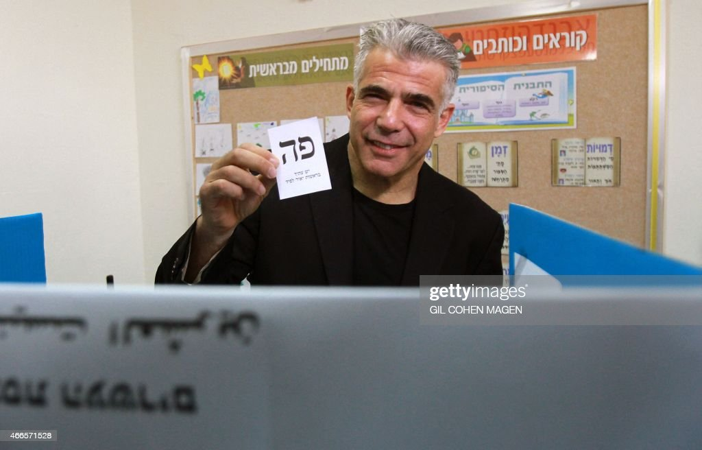 Israeli MP and chairperson of center-right Yesh Atid party, Yair Lapid, prepares to cast his ballot at a polling station, on March 17, 2015 in Tel Aviv. Voting polls opened for unpredictable elections to determine whether Israelis still want incumbent Prime Minister Benjamin Netanyahu as leader, or will seek change after six years. AFP PHOTO / GIL COHEN MAGEN