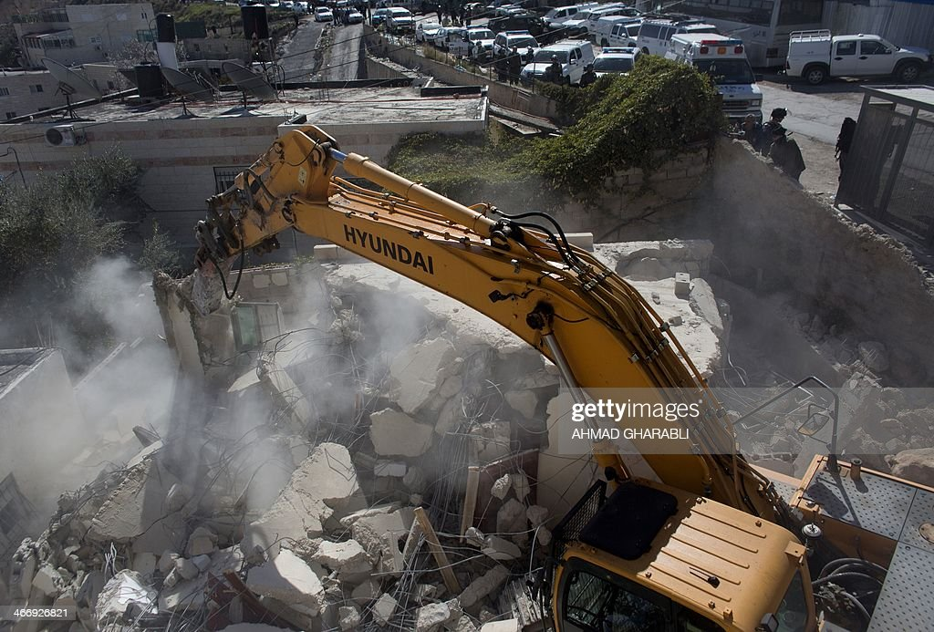Israeli municipality workers use a mechanical digger to demolish a house belonging to a Palestinian family that the authorities say was built without municipal permission, in the Arab east Jerusalem neighborhood of Jabel Mukaber, on February 5, 2014. Israel pushed forward with plans for more than 550 new homes in three settlement neighbourhoods of annexed east Jerusalem, the city council said.