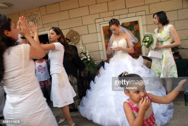 Israeli Muslim women dance around Sanaa Farhat as she greets friends and family outside of her home during her wedding ceremony of Israeli Arabs in...