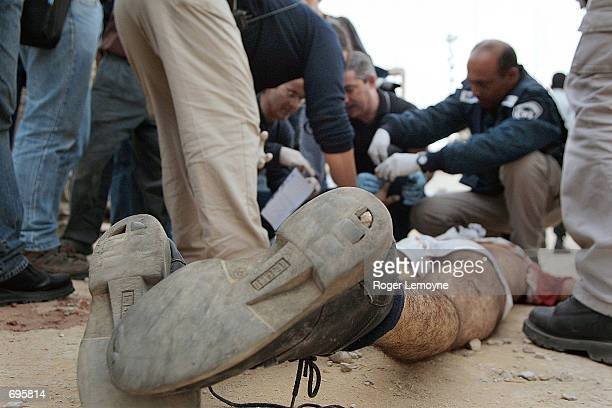 Israeli officials examine the body of a Palestinian gunman who was killed in a gun battle with Israeli security forces February 10 2002 outside the...
