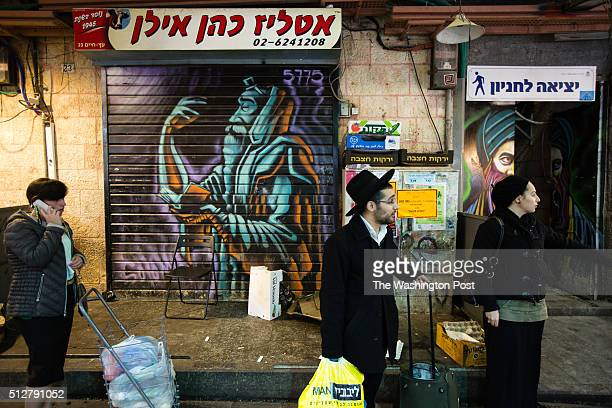 Israeli orthodox and ultraOrthodox shoppers stand in front of a graffiti depicting a Jewish man praying which was painted over a closed shutter at...