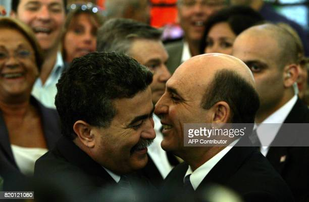 Israeli outgoing defence minister Shaul Mofaz hugs Amir Peretz Israel's first 'civilian' defence minister during a ceremony at Israeli presidents'...