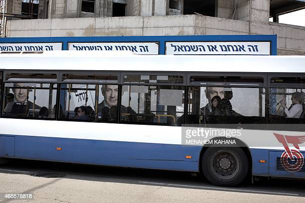 Israeli passengers on a bus pass by campaign posters showing Israeli Prime Minister and Likud party's candidate running for general elections...