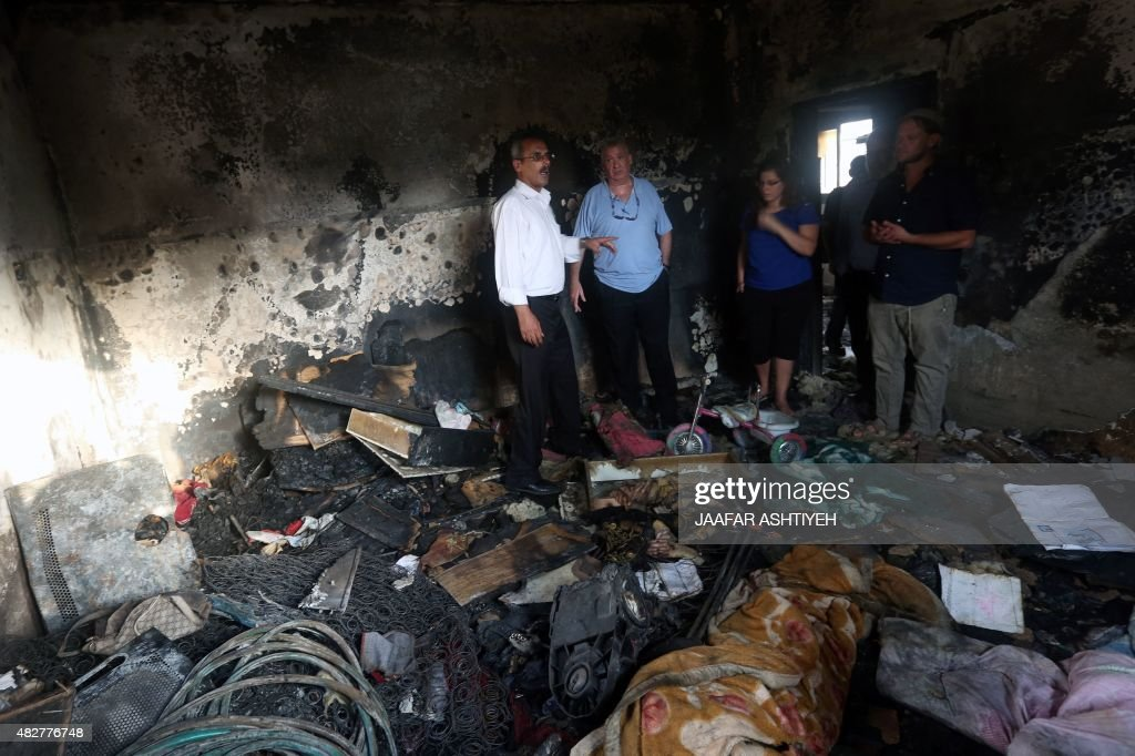 Israeli peace activists stand in the Dawabsha family's home set on fire by suspected Jewish extremists and where a Palestinian toddler was burned to...