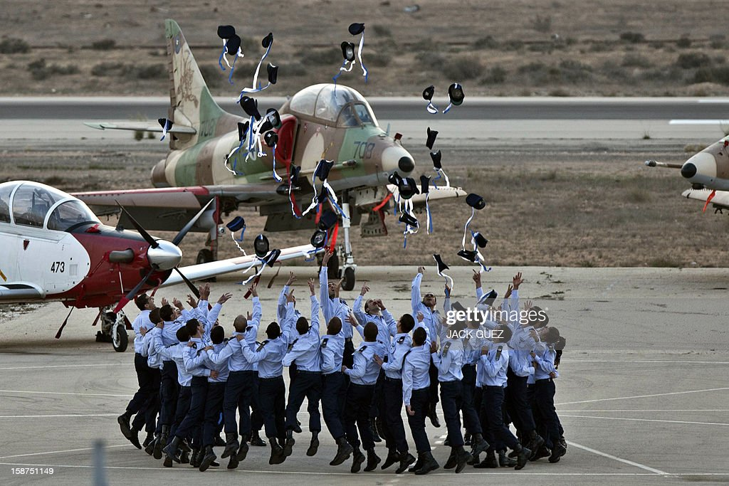 Israeli pilots throw their hats in the air as they celebrate at their graduation ceremony at the Hazerim air force base in the Negev desert, near the southern Israeli city of Beersheva, on December 27, 2012. AFP PHOTO / JACK GUEZ