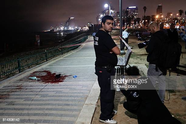 Israeli police and journalists gather at the scene of a stabbing attack on March 8 2016 in the neighbourhood of Jaffa in the Israeli city of Tel Aviv...